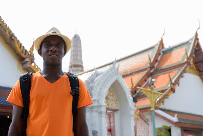 Glücklicher afrikanischer touristischer Mann, der am buddhistischen Tempel lächelt und denkt lizenzfreies stockfoto