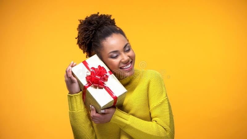 Glücklicher afrikanischer weiblicher haltener Präsentkarton mit rotem Bogen, Geburtstagsgeschenküberraschung lizenzfreie stockfotografie