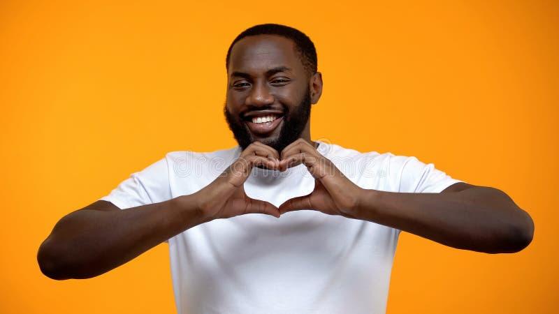 Gl?cklicher afro-amerikanischer Mann, der Herzgeste an der Kamera, romantische Stimmung zeigt lizenzfreie stockfotografie