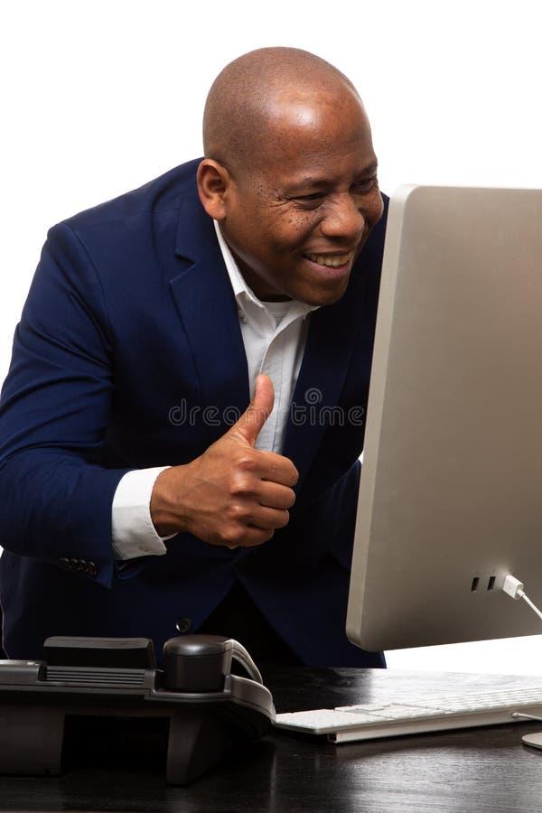 Glücklicher Afroamerikaner-Geschäftsmann Looks At Computer mit den Daumen oben lizenzfreie stockfotos