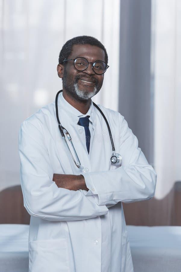 glücklicher Afroamerikanerdoktor im weißen Mantel mit Stethoskop und gekreuzt lizenzfreies stockfoto