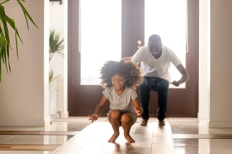 Glücklicher Afroamerikanermann, der zu Hause lustiges Spiel mit Tochter spielt lizenzfreie stockbilder