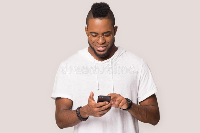 Gl?cklicher Afroamerikanermann-Griff Smartphone gute Mitteilung erhalten lizenzfreies stockbild