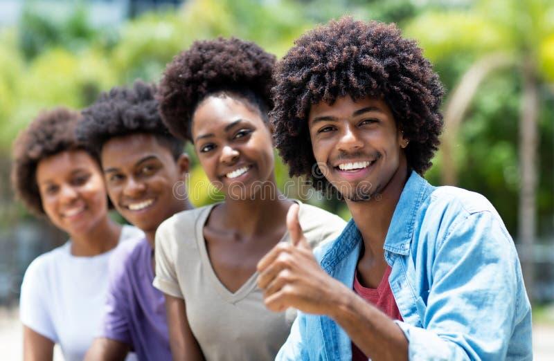 Glücklicher Afroamerikanermann mit Gruppe jungen Erwachsenen in der Linie stockfotografie