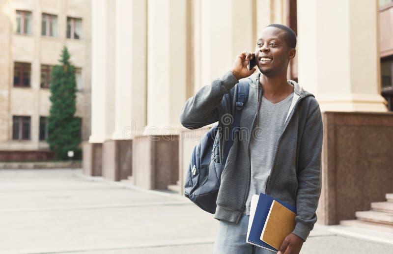 Glücklicher Afroamerikanerstudent, der auf Smartphone im Campus spricht lizenzfreie stockbilder