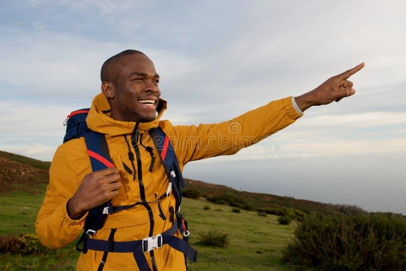 Glücklicher Afroamerikanerwanderer, der draußen Finger in Natur zeigt lizenzfreies stockfoto