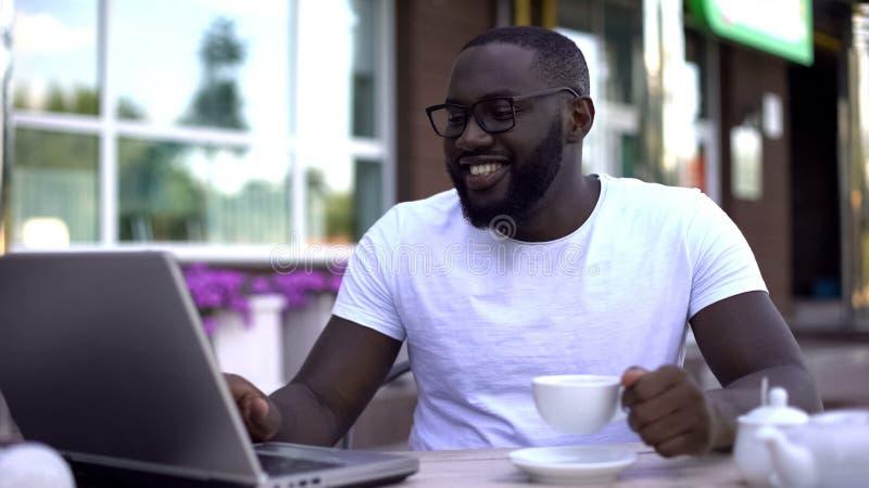 Glücklicher afroer-amerikanisch Mann, der mit Verwandten auf dem Laptop, sitzend im Restaurant simst lizenzfreie stockfotos