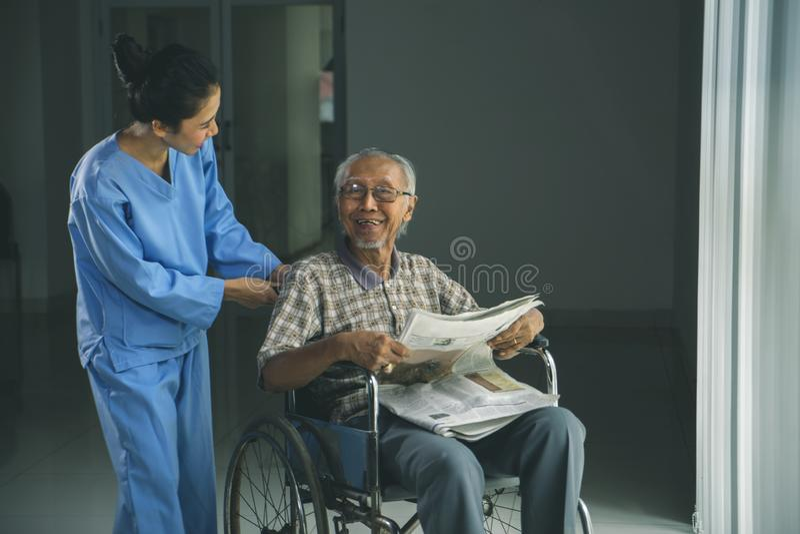 Glücklicher alter Mann sitzt auf einem Rollstuhl mit seiner Krankenschwester lizenzfreie stockfotos