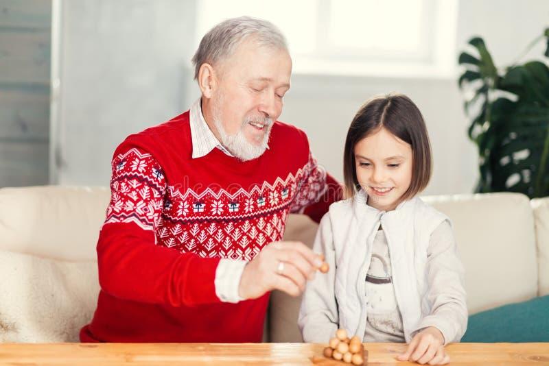 Glücklicher alter Mann und kleines ein Mädchen, das Spaß beim Sitzen auf dem Sofa hat lizenzfreies stockbild