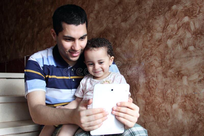 Glücklicher arabischer ägyptischer Vater mit der Tochter, die selfie nimmt stockbild