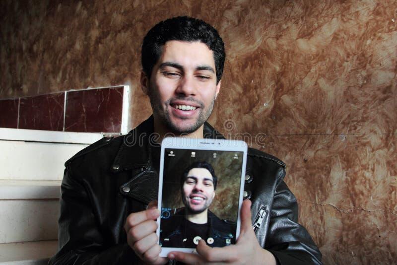Glücklicher arabischer junger Geschäftsmann in der Jacke, die selfie nimmt lizenzfreie stockfotografie