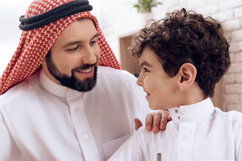 Glücklicher arabischer Vater hält kleinen Sohn durch Schulter stockbild