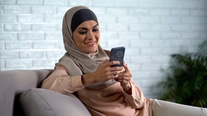 Glücklicher arabischer weiblicher in einer Liste verzeichnender Smartphone Foto der sozialen Netzwerke, Hausfraufreizeit stockbild