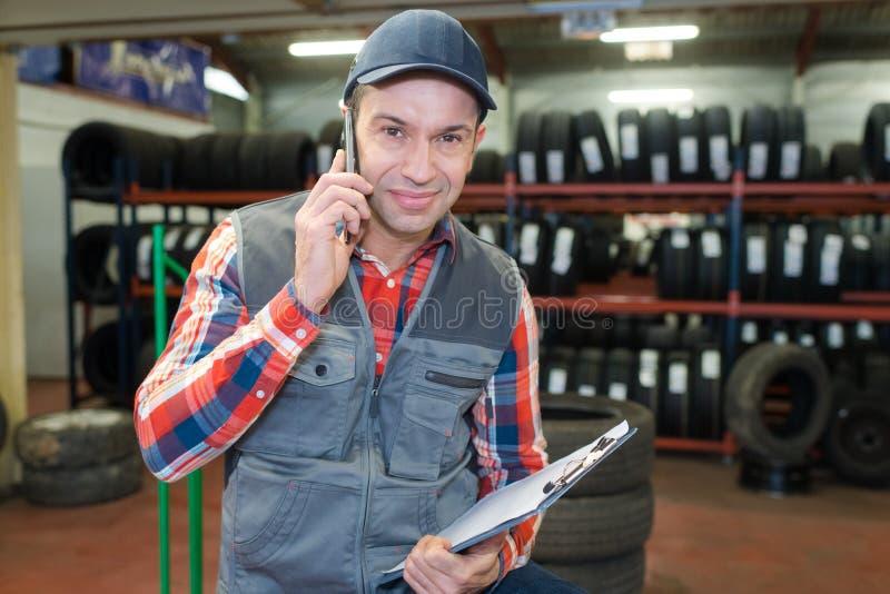 Glücklicher Arbeiter am Telefon in der Reifenreparatur stockfotografie