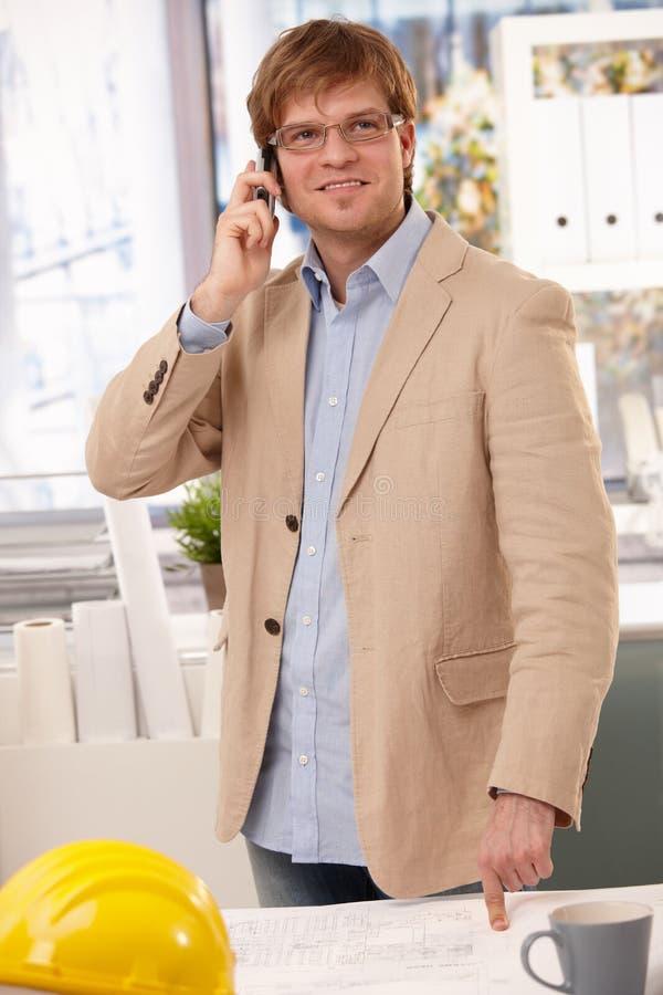 Glücklicher Architekt, der am Telefon bei Tisch zeigt spricht stockbilder