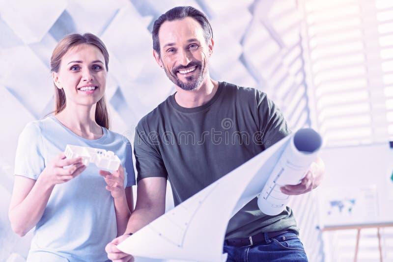 Glücklicher Architektenholdingplan während seine Kollegestellung mit Hausminiatur stockfoto