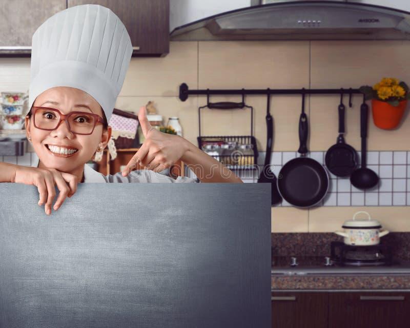 Glücklicher asiatischer Chef, der Menüzeichen auf Tafel zeigt stockbilder