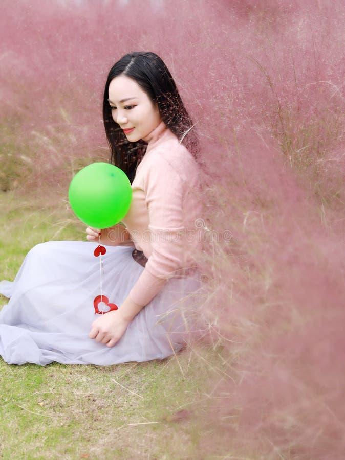 Glücklicher asiatischer Chinesinmädchengefühl-Freiheitstraum, Blumenfeld-Fallparkgrasrasen-Hoffnungsnatur zu beten las Buchballon stockfotografie