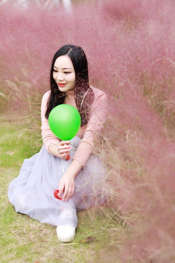 Glücklicher asiatischer Chinesinmädchengefühl-Freiheitstraum, Blumenfeld-Herbstfallparkgrasrasen-Hoffnungsnatur zu beten las Buch lizenzfreies stockbild