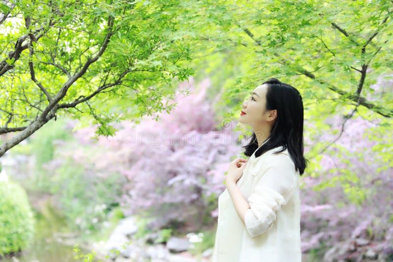 Glücklicher asiatischer chinesischer hübscher Frauenstand unter Baum in der Natur im Frühjahr im Freien lizenzfreie stockfotos