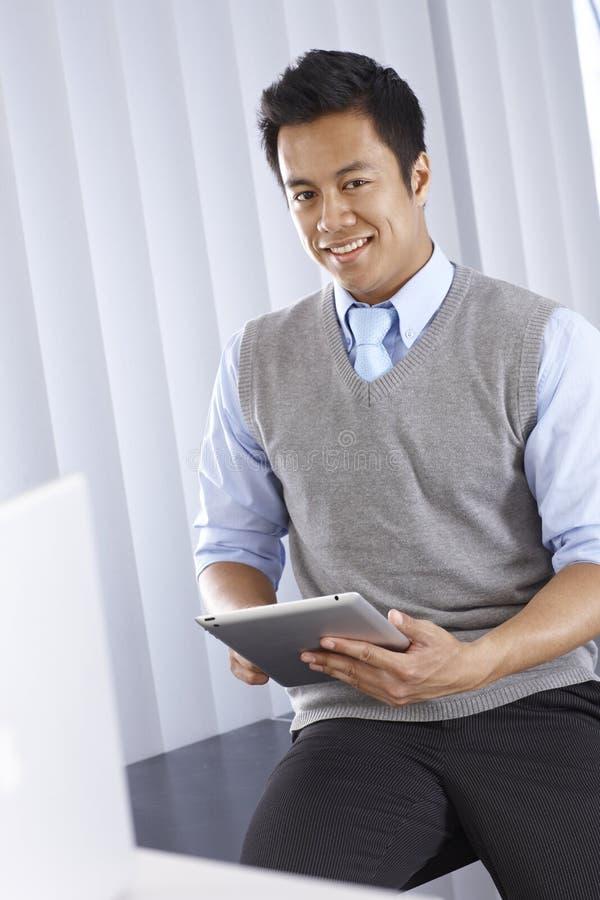 Glücklicher asiatischer Geschäftsmann mit Tablet-Computer lizenzfreie stockbilder