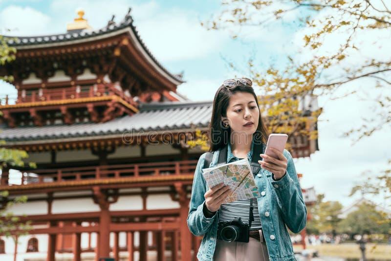 Glücklicher asiatischer Tourist, der Informationen über Linie sucht lizenzfreie stockbilder