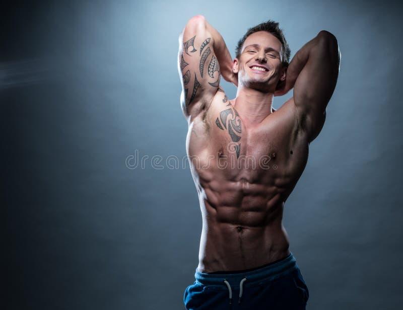 Glücklicher athletischer Mann mit den Händen unterstützen an von seinem Kopf stockfoto
