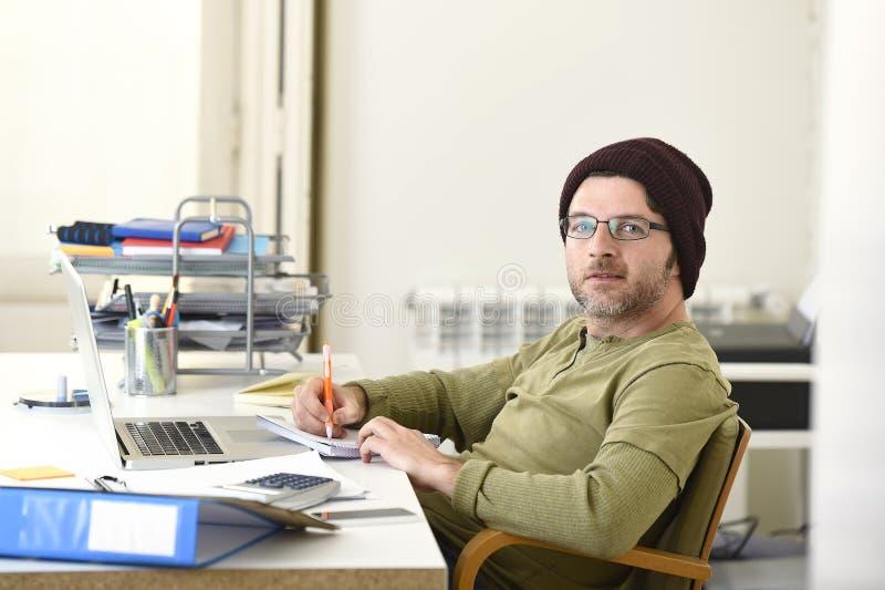 Glücklicher attraktiver Hippie-Geschäftsmann, der zu Hause mit Büro des Computerlaptops arbeitet stockfotografie