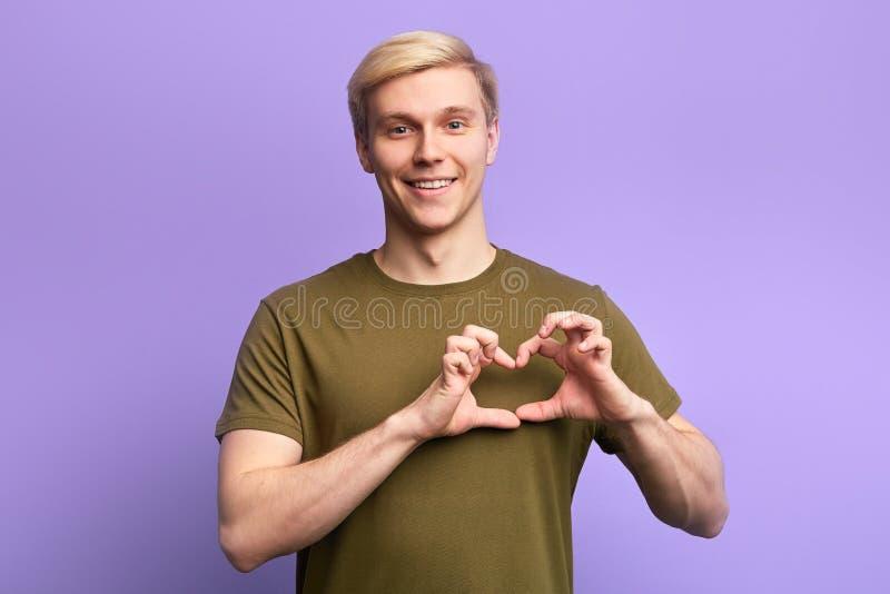 Glücklicher attraktiver junger Mann, Händchenhalten in der Herzgeste, lizenzfreie stockfotos