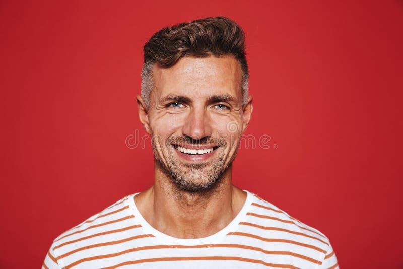 Glücklicher attraktiver Mann mit Stoppel in gestreiftem T-Shirt an lächelnd stockfotografie