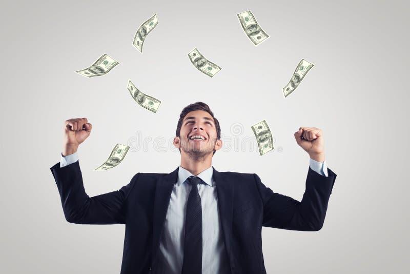 Glücklicher aufgeregter Geschäftsmann, der oben Hände anhebt und oben unter Geldregen schaut lizenzfreies stockbild