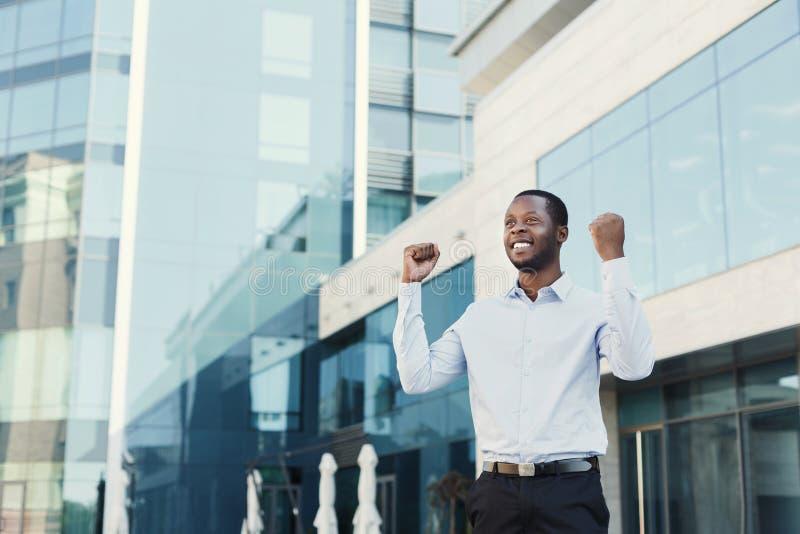 Glücklicher aufgeregter Geschäftsmann feiern Sieger, schwarzer Mann draußen lizenzfreies stockbild