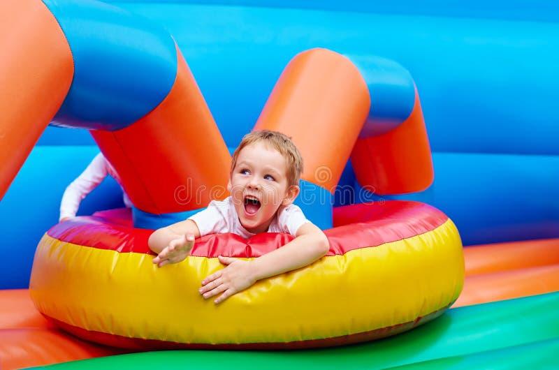 Glücklicher aufgeregter Junge, der Spaß auf aufblasbarem Anziehungskraftspielplatz hat stockfoto