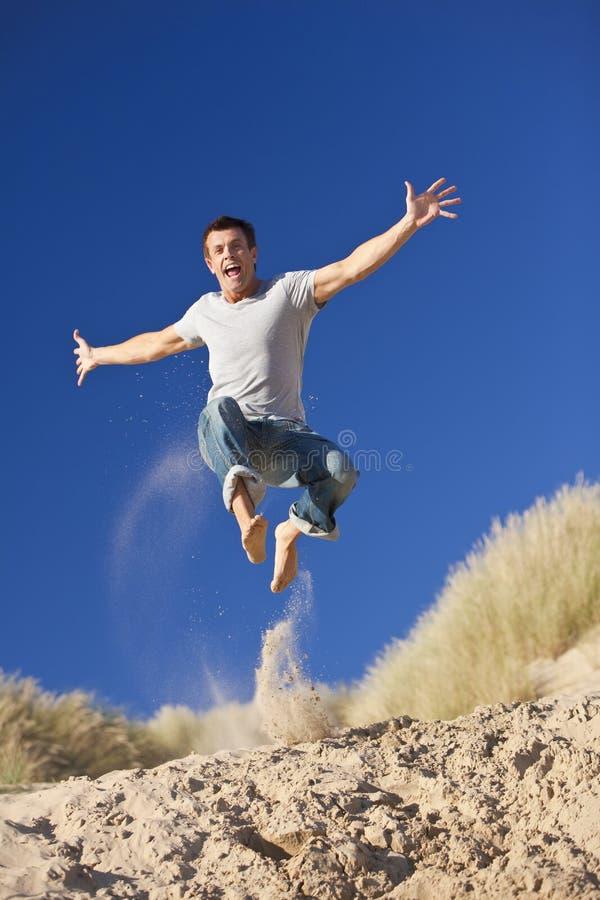 Glücklicher aufgeregter junger Mann, der auf einen Strand springt stockfotografie
