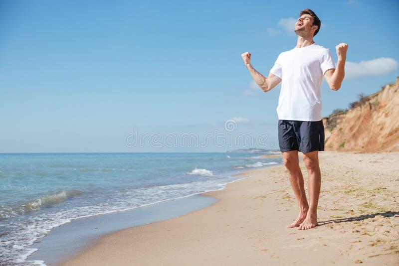 Glücklicher aufgeregter Mann mit den angehobenen Händen Erfolg auf Strand feiernd lizenzfreie stockfotos