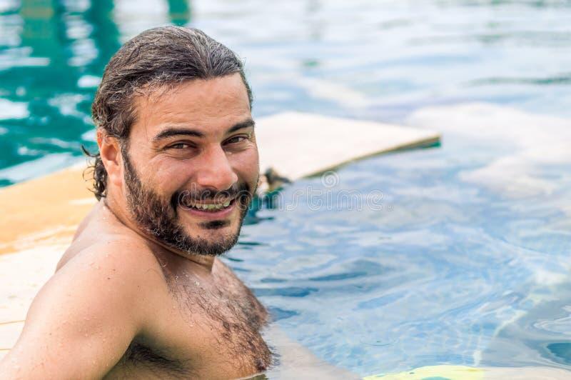 Glücklicher bärtiger Mann, der im Swimmingpool im Erholungsort sich entspannt lizenzfreies stockbild