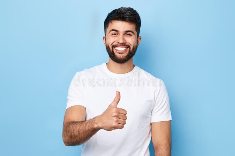 Glücklicher bärtiger Mann im stilvollen weißen T-Shirt mit dem Vertretungsdaumen des strahlenden Lächelns oben stockbild