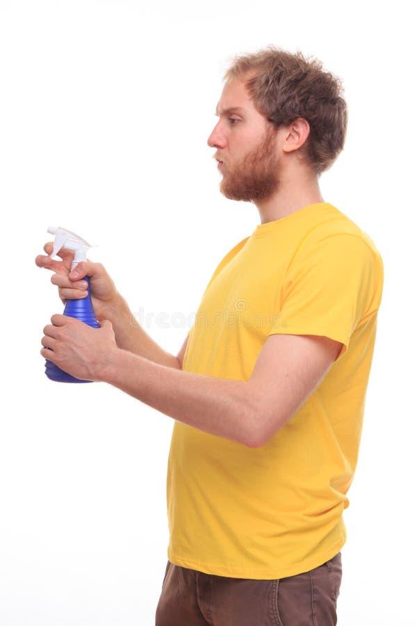 Glücklicher bärtiger Mann wäscht sich mit Spray und Gummi stockfotografie