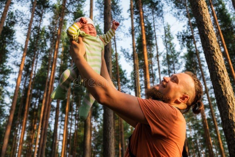 Glücklicher bärtiger Vater, der seine 3 Monate alten schläfrige Baby auf seinen ausgestreckten Armen hält stockbilder