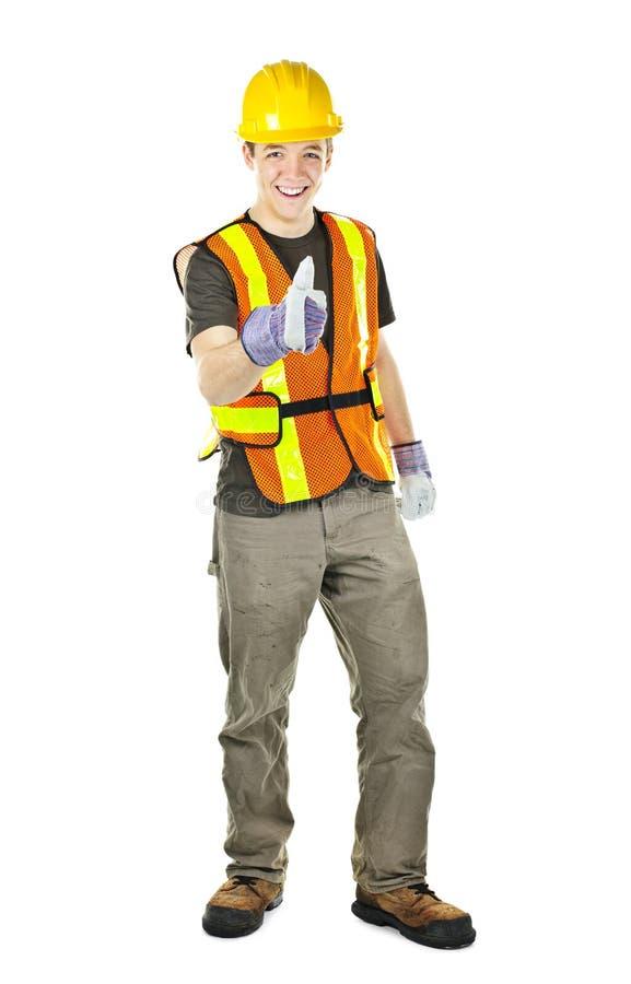 Glücklicher Bauarbeiter, der sich Daumen zeigt stockfoto