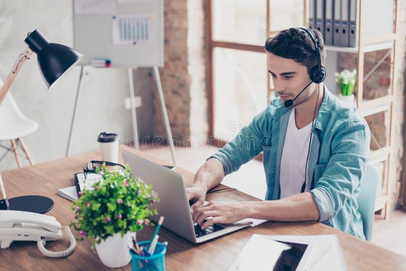 Glücklicher Betreiber des Call-Centers in den Kopfhörern, die mit dem clie sprechen lizenzfreies stockbild