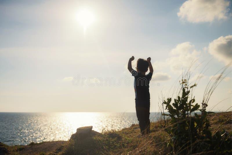 glücklicher Blick des kleinen Jungen in Sonnenuntergang und Meer stockfotografie