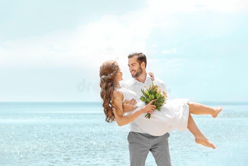 Glücklicher Bräutigam, der Braut in seinen Armen hält stockbilder