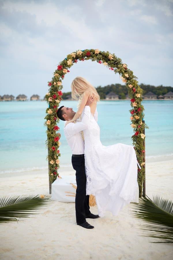 Glücklicher Bräutigam hält Braut auf seinen Händen unter Hochzeitszeremoniebogen auf Tropeninselstrand auf Malediven Türkisozean stockbild