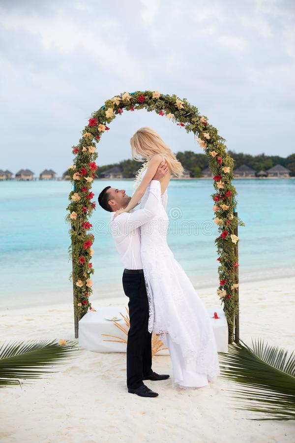 Glücklicher Bräutigam hält Braut auf seinen Händen unter Hochzeitszeremoniebogen auf Tropeninselstrand auf Malediven Türkisozean lizenzfreie stockbilder