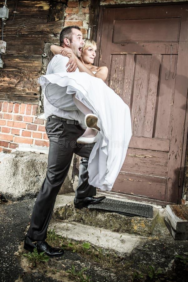 Glücklicher Bräutigam holt die Braut zum Haus stockbild