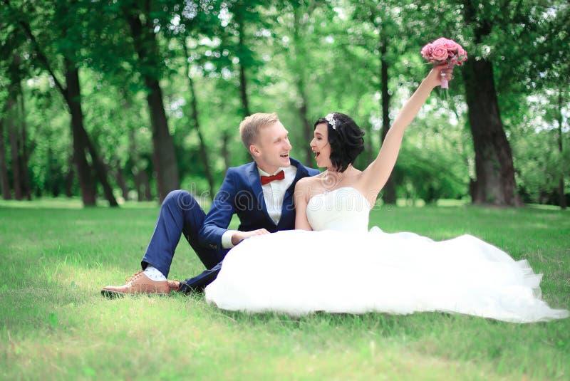 Glücklicher Bräutigam und Braut, die im Rasen sitzt lizenzfreies stockbild