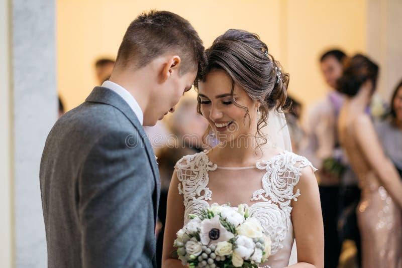 Glücklicher Bräutigam und Braut im Registeramt Hochzeitsgäste in einem unscharfen Hintergrund stockfotografie