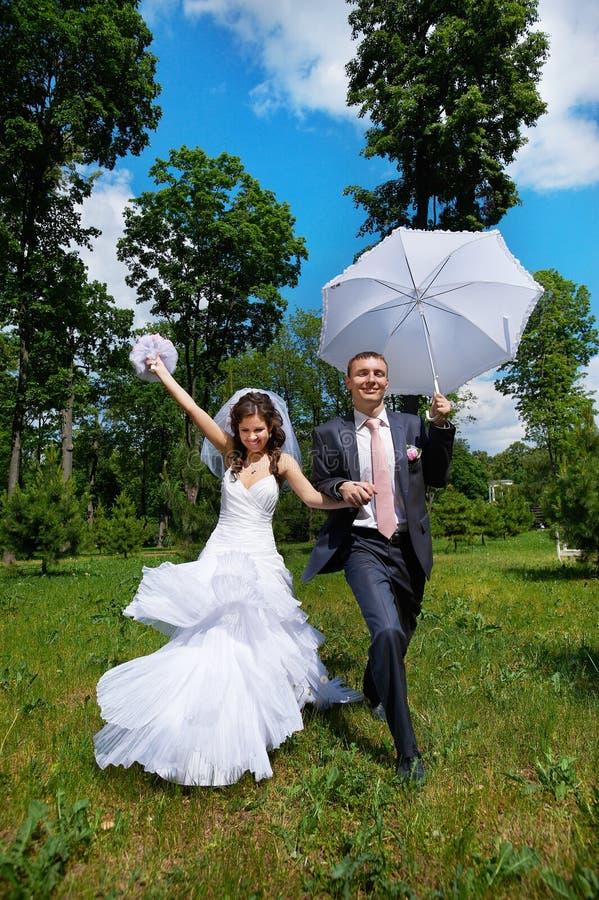 Glücklicher Bräutigam und glückliche Braut mit Regenschirm im Sommer parken stockfotos