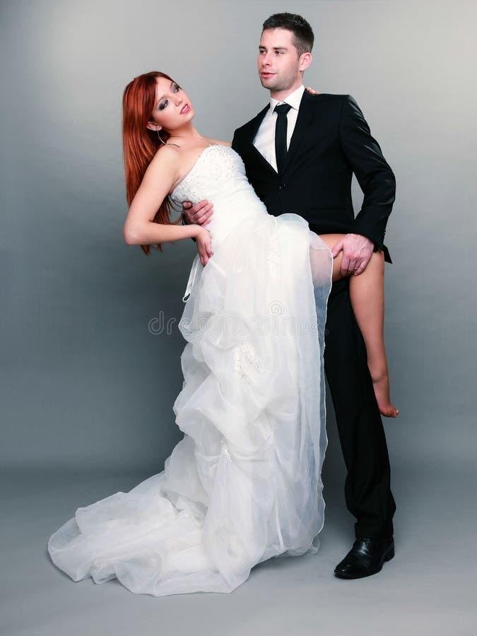 Glücklicher Brautbräutigam des verheirateten Paars auf grauem Hintergrund stockbilder